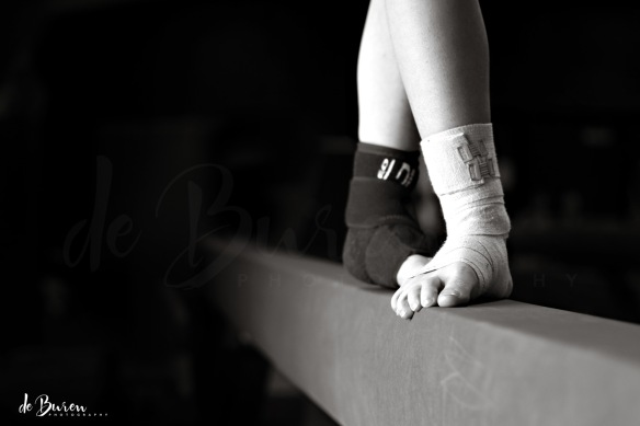dedicated young gymnast with ankles wrapped standing on balance beam